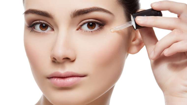 woman applying pure hydration syrum to face